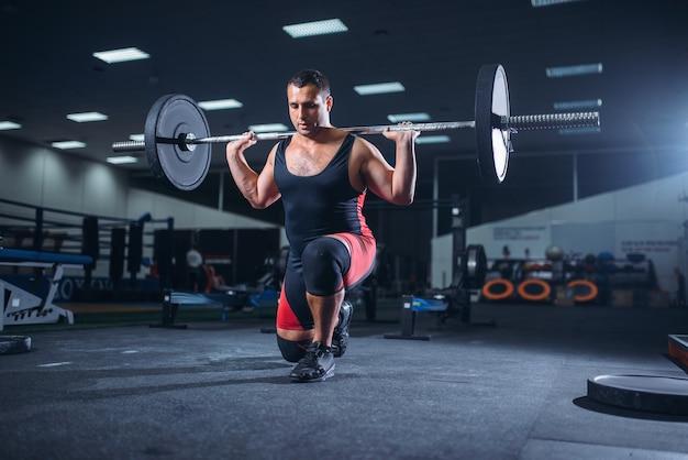 Sollevatore di pesi forte che fa squat con un bilanciere in palestra