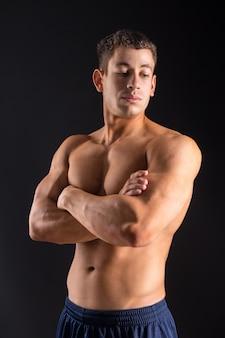 Sollevatore di pesi giovane culturista sportivo bello con un corpo perfetto