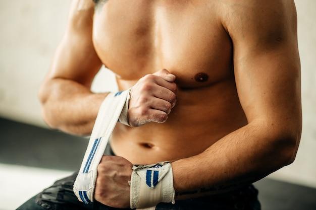 Sollevatore di pesi muscolare che avvolge le mani e che prepara per l'allenamento in una palestra.