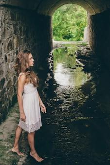 Solo bella ragazza con i capelli ricci naturali in abito bianco in antico tunnel allagato con pareti pietrose. principessa solitaria nel vecchio castello. ragazza del sognatore in lungo tunnel con acqua. muschio nel vecchio tunnel.