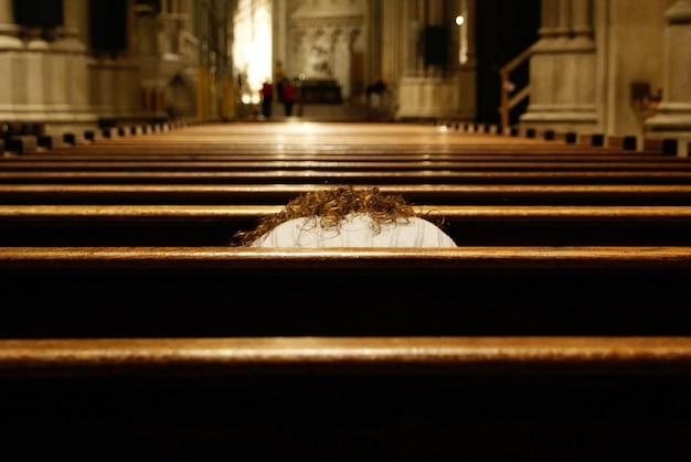 Solo donna cattolica che prega prostrata all'interno di un tempio cristiano.