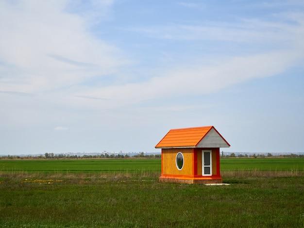 Solo piccola casa arancione in legno con porta bianca, finestra rotonda nel campo verde e cielo blu con nuvole