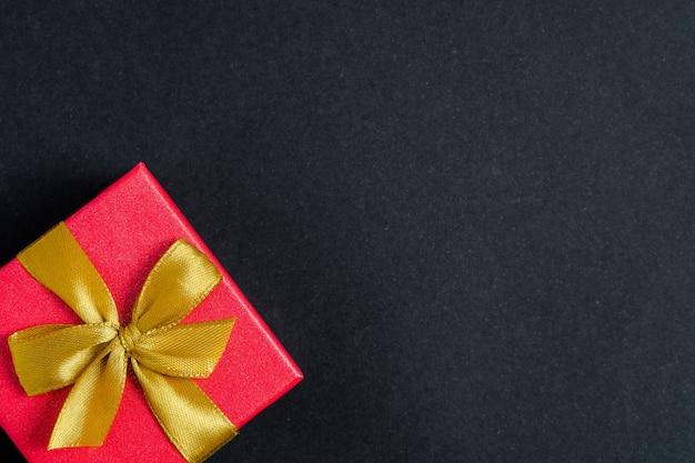 Solo un regalo su uno sfondo nero con spazio per il testo a destra.