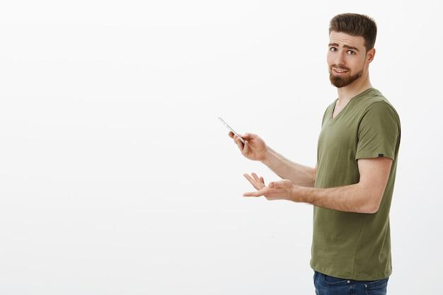 Solo un secondo, vedi che sono impegnato. ritratto di giocatore di fidanzato carino irritato in piedi di profilo con lo smartphone che gira infastidito perché distratto da un'app interessante sul muro bianco