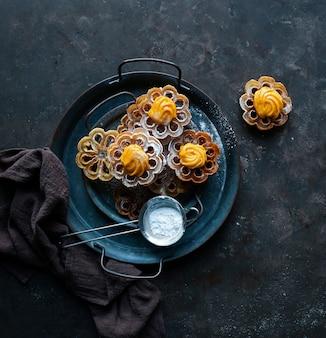 Solteritas o flores de carnaval con crema, con panna, biscotti colombiani per natale e pasqua