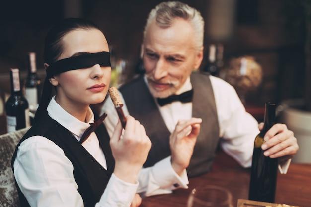 Sommelier esperto con bendaggio sugli occhi annusare il sughero.