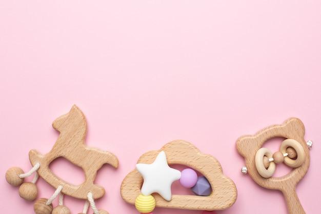 Sonagli e giocattoli di legno del bambino sul rosa