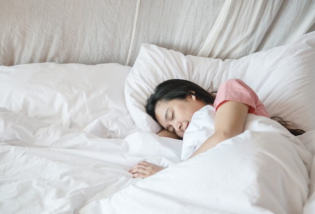Sonno asiatico della donna del primo piano sul letto sotto la coperta nel fondo della camera da letto di mattina