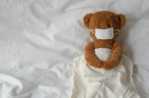 Sonno d'uso della maschera del giocattolo dell'orsacchiotto sul letto. stai a casa lontano dal concetto di virus.