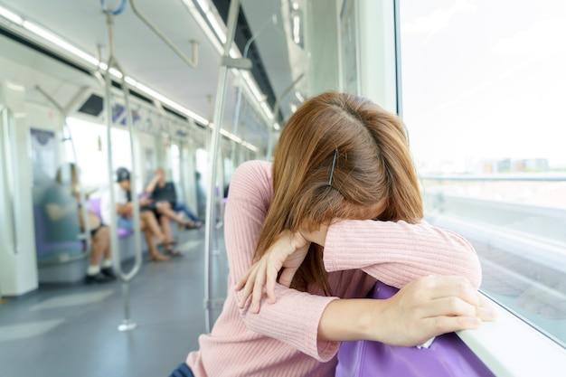 Sonno della giovane donna mentre prendendo il treno di alianti.