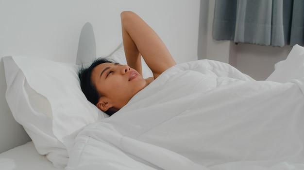 Sonno indiano asiatico di signora nella sala a casa. la giovane ragazza asiatica che si sente felice si rilassa il resto che si trova sul letto, si sente a proprio agio e calmo in camera da letto a casa alla mattina.