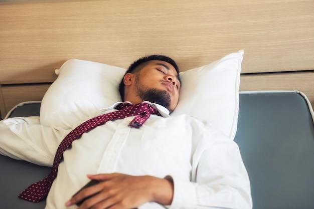 Sonno indiano stanco dell'uomo d'affari sul letto dell'hotel