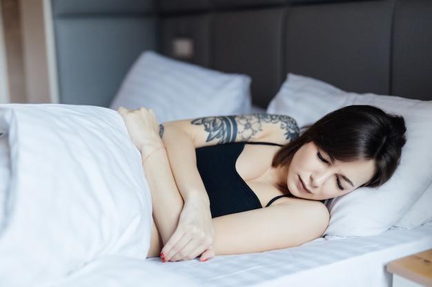 Sonnolenta giovane donna sdraiata a letto non vuole svegliarsi