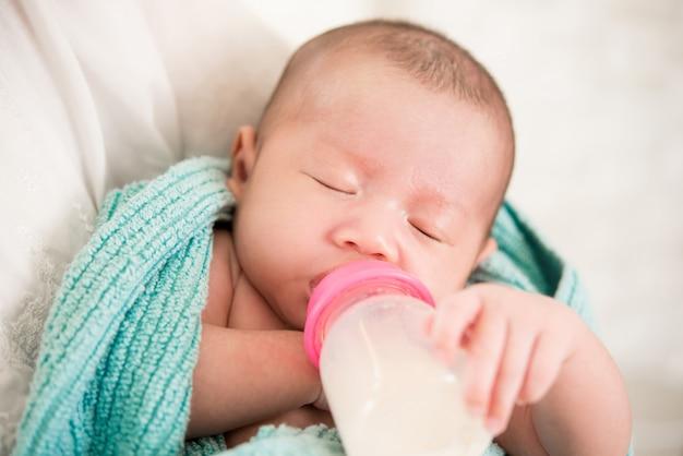 Sonnolento carino neonato beve il latte dalla bottiglia