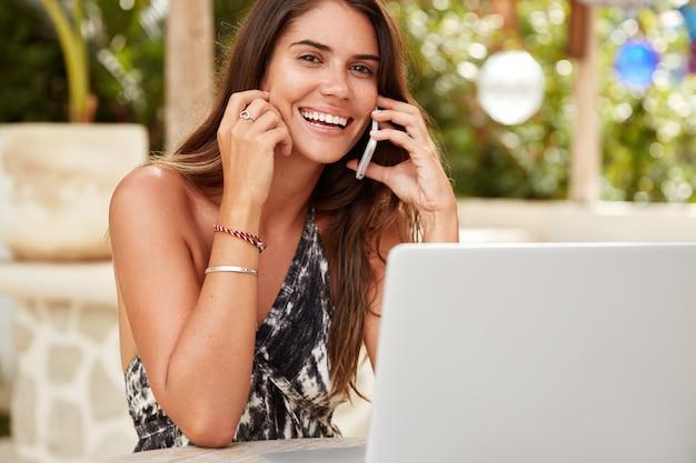 Sono contento che reclutatore femminile fa un'offerta di lavoro al candidato tramite telefono cellulare, controlla la documentazione sul computer portatile