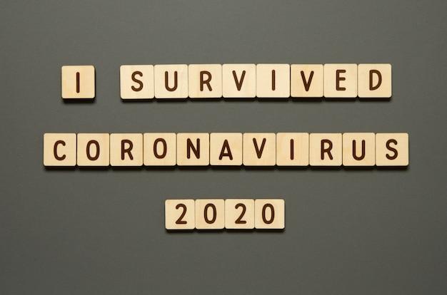 Sono sopravvissuto a coronavirus 2020 - parole da blocchi di legno con lettere. vista dall'alto