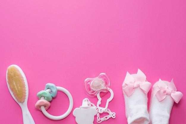 Soother degli accessori della neonata, giocattolo di legno, calzini e massaggiagengive su fondo rosa con lo spazio della copia. vista dall'alto, piatto.