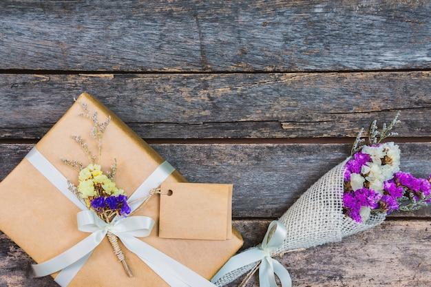 Sopra il nastro bianco del contenitore di regalo marrone e fiori d'annata con l'etichetta su legno