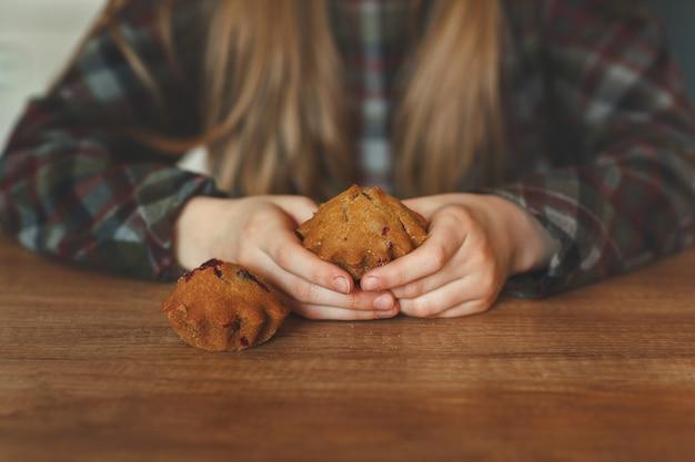 Sopra il tavolo di legno, le mani dei bambini reggono deliziosi cupcakes