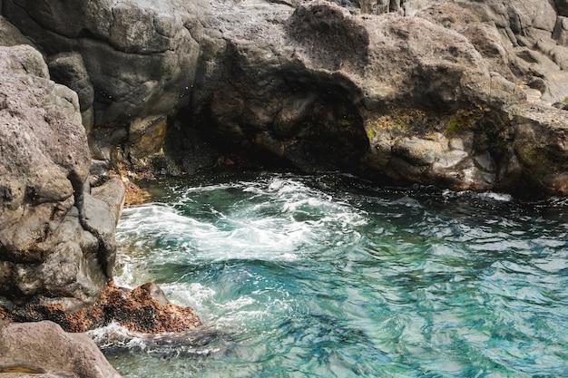 Sopra l'acqua ondulata del primo piano di vista alla riva rocciosa