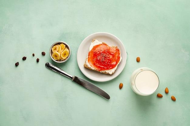 Sopra la disposizione vista con gustosa colazione su sfondo verde