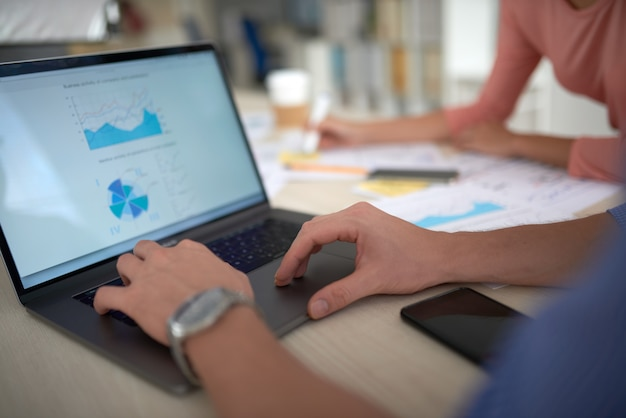 Sopra la spalla dello schermo del laptop che mostra gli elementi grafici delle statistiche finanziarie