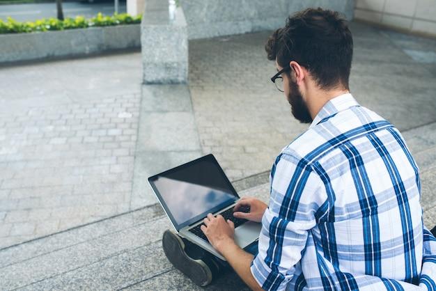 Sopra la spalla di codifica uomo sul computer portatile