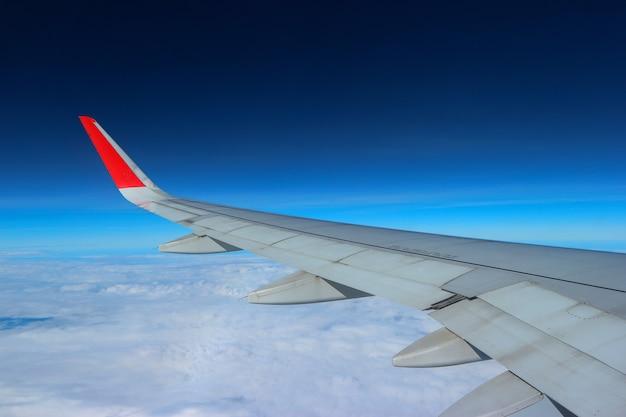 Sopra la vista del cielo blu della nuvola dalla finestra dell'aeroplano.
