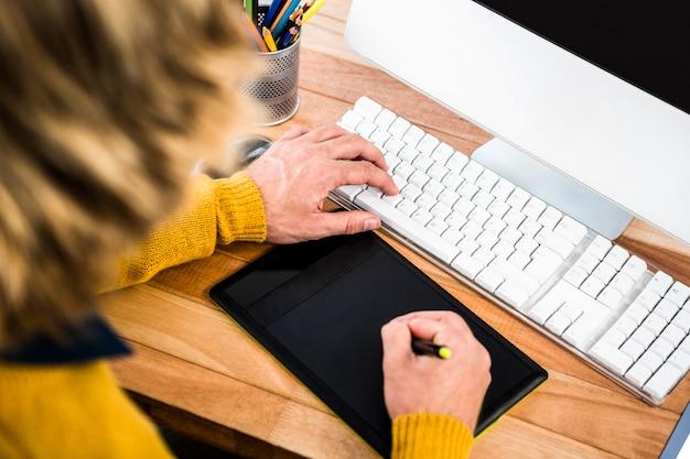 Sopra la vista della spalla dell'uomo d'affari facendo uso della grafica della compressa nel suo ufficio