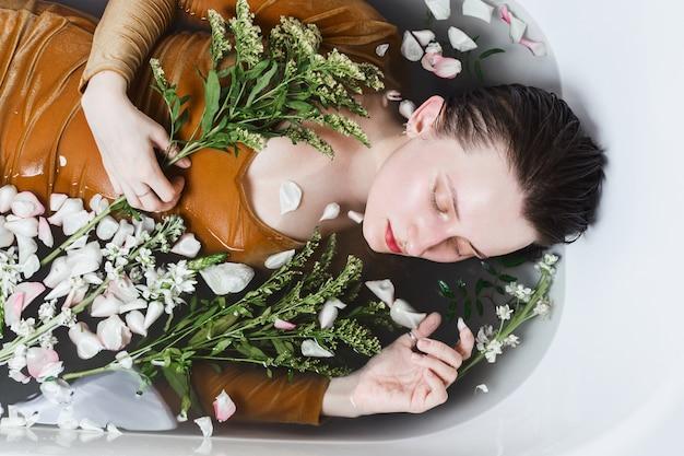 Sopra ritratto di giovane donna adulta che giace nella vasca da bagno pieno di carbone e fiori