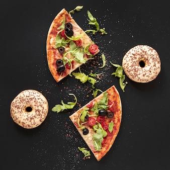 Sopra vista disposizione con fette di pizza e ciambelle