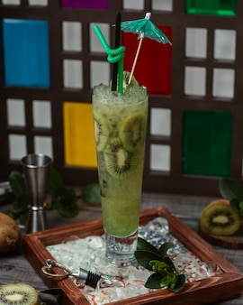 Sorbetto al kiwi cocktail all'interno del bicchiere con ombrellone e cubetti di ghiaccio.