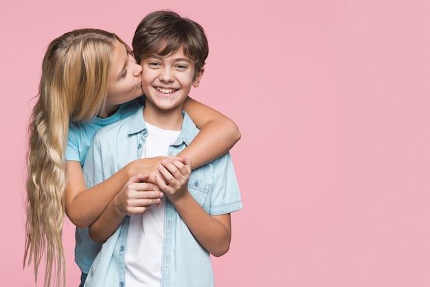 Sorella che bacia il fratello sulla guancia
