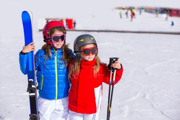 Sorella delle ragazze del bambino nella neve di inverno con l'attrezzatura dello sci