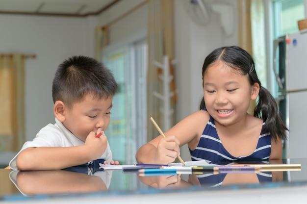 Sorella e fratello dipingono colore su carta a matita.