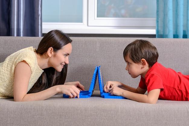 Sorella e fratello minore, giocano una nave da guerra, sdraiati sul divano nella stanza e guardati l'un l'altro
