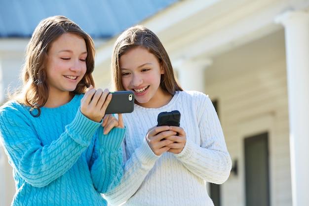 Sorella gemelli divertendosi con smartphone tecnologia