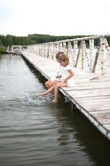 Sorelle calcia i piedi sul lago, infanzia, tono leggero