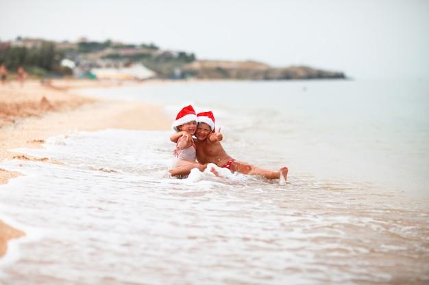 Sorelle caucasiche abbronzate dei bambini in cappelli di santa sulla spiaggia con sabbia gialla, natale del mare