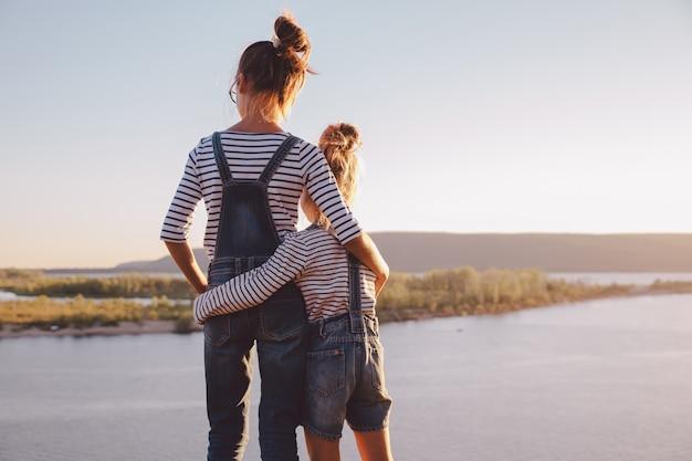 Sorelle che abbracciano mentre osservano la natura
