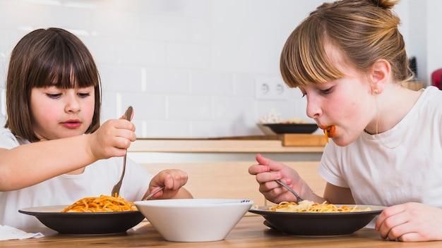 Sorelle che mangiano pasta deliziosa in cucina