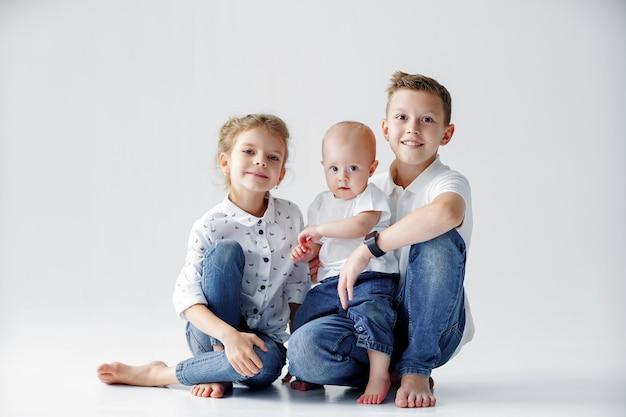Sorelle e fratello felici sono seduti sul pavimento
