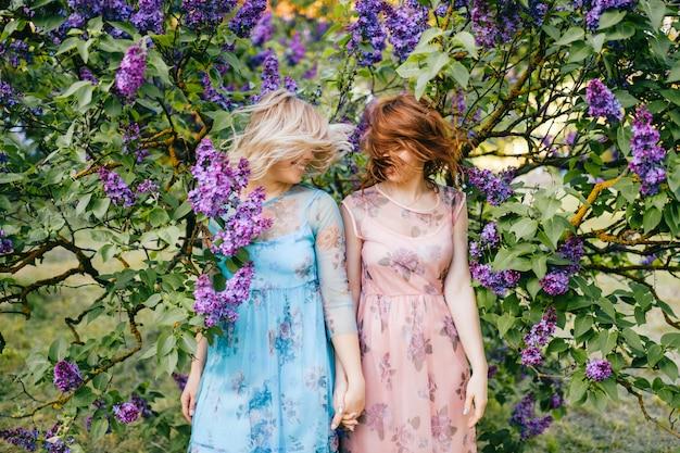Sorelle gemelle espressive in bellissimi abiti che scuotono la testa nel parco fiorito estivo.