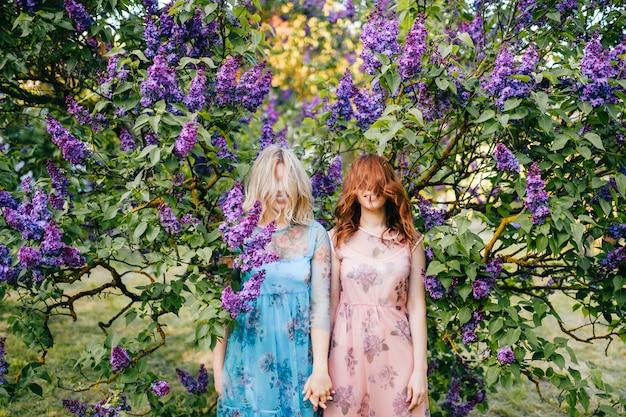 Sorelle gemelle espressive in bellissimi abiti in piedi in cespugli lilla con i capelli che coprono il viso.