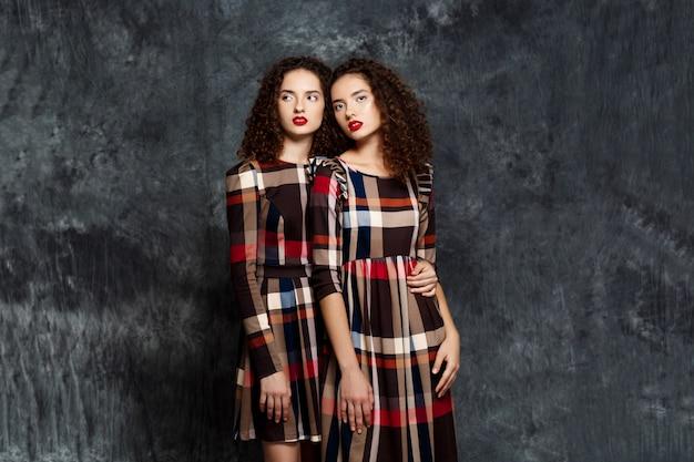 Sorelle gemelle in abiti in posa sul grigio