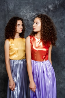 Sorelle gemelle in abiti luminosi in posa sul grigio