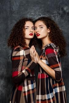 Sorelle gemelle in posa sul grigio