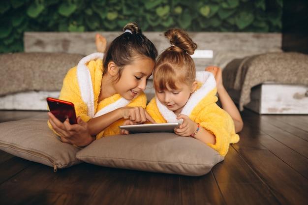 Sorelle sdraiato sul pavimento con telefono e tablet