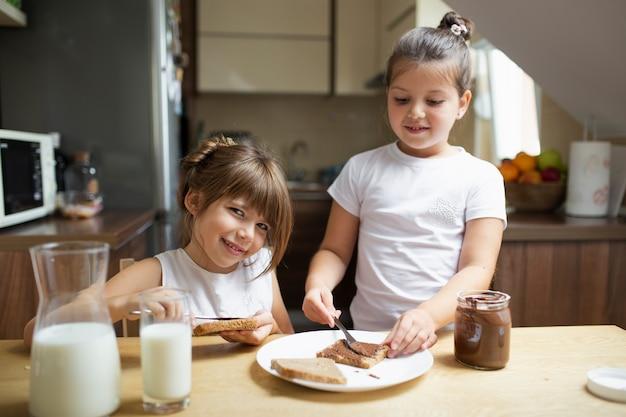 Sorelline che mangiano prima colazione in mattina