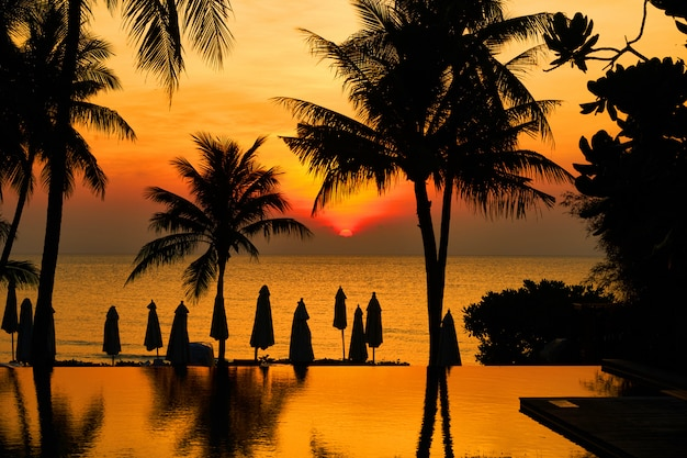 Sorgere del sole di fronte alla spiaggia con silhouette cocco o palma, ombrellone e piscina con la riflessione